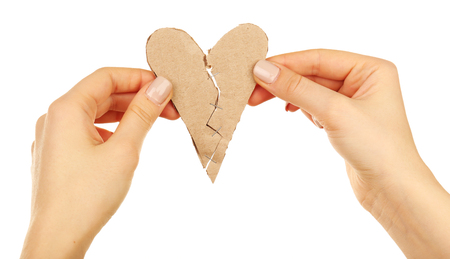 Female hands holding broken heart stitched with staples isolated on white