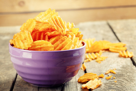 Delicious potato chips in bowl on wooden table close-up