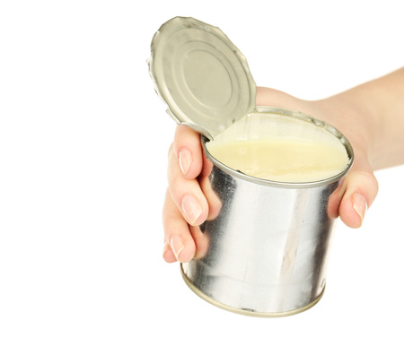 Female hand holding tin can of condensed milk isolated on white Banco de Imagens