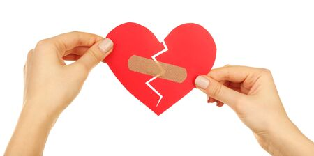 Female hands holding broken heart with plaster isolated on white Stock Photo