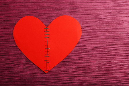 Broken heart stitched with staples on colour background Stock Photo