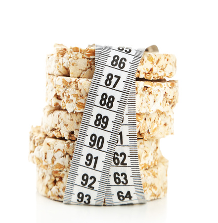 Fresh crispbread with measuring tape, isolated on white - diet concept Stockfoto