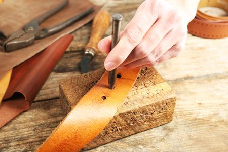 Repairing leather belt in workshop Stockfoto