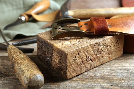 Craft tools with leather belt on table close up Stock Photo