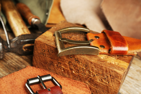 Craft tools with leather belt on table close up Foto de archivo