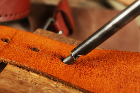 Leather belt and punches on table close up