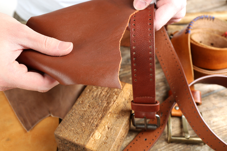 Repairing leather belt in workshop Stock Photo