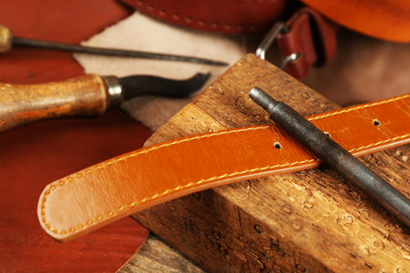 Craft tools with leather belt on table close up Archivio Fotografico