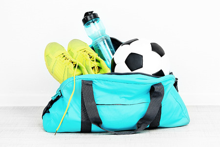 Sports bag with sports equipment in room Imagens