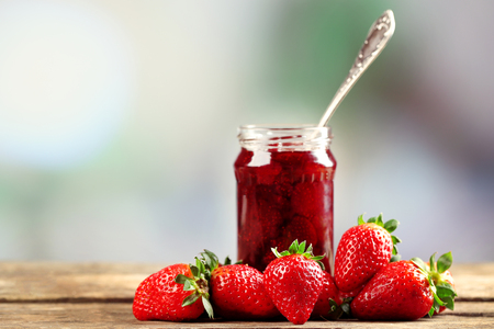 Jar of strawberry jam with berries on table on bright background