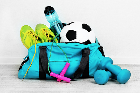 Sports bag with sports equipment in room Archivio Fotografico