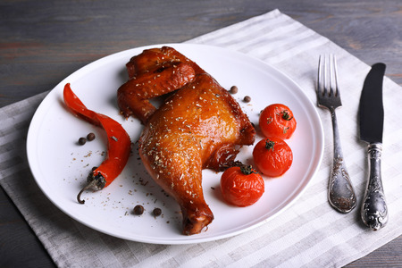 Smoked chicken leg  with vegetables on plate on table close up Banque d'images