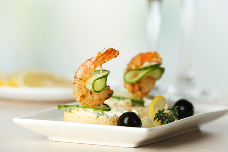 Appetizer canape with shrimp and olives on table on light background