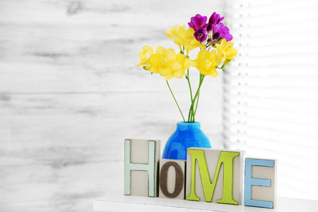 Home in colorful letters and spring flowers in light white interior