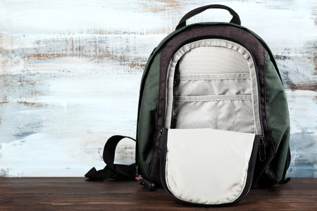Backpack on wooden background Stock Photo