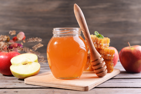 Delicious honey with apple on table on wooden background Stock Photo