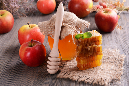 Delicious honey with apple on table close-up