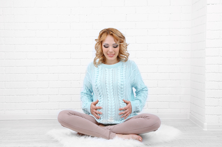 Young pregnant woman sitting on carpet on light background Stock Photo