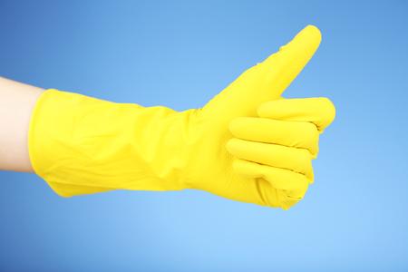Rubber glove on hand, on blue background Banco de Imagens