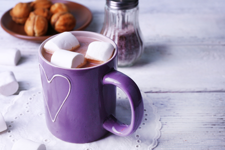 Cup of cocoa with marshmallows and cookies on wooden table, closeup Banco de Imagens