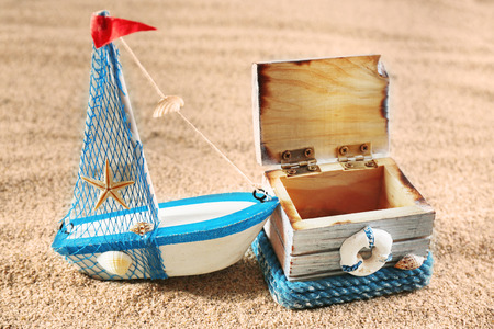 Toy model of ship with wooden box on sea sand background