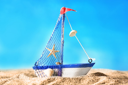 Toy model of ship on sand on blue background Stock Photo