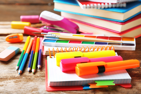 Bright school stationery on old wooden table Imagens