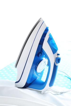 Iron on ironing board on light background Imagens