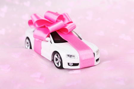New car with bow as present  on pink background