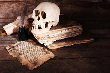 Still life with human skull, retro book and quill on wooden background Banque d'images