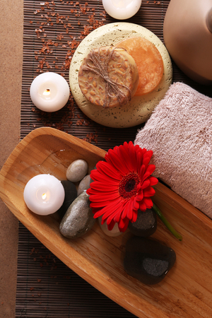 Composition of spa stones, sea salt and massage bags on wooden table, on light color background 写真素材