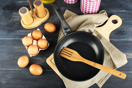 Still life with eggs and pan on wooden table, top view Stock Photo