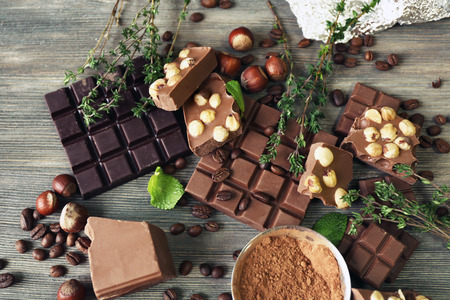 Set of chocolate with nuts, herbs and coffee beans on wooden table, closeup