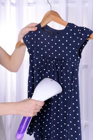 Women steaming dress in room