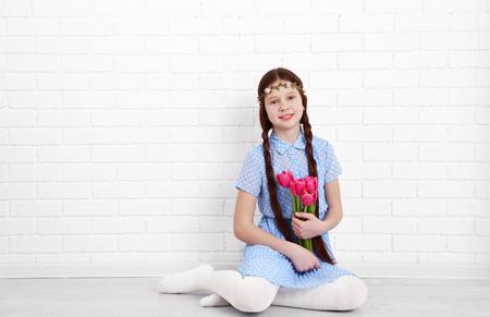 Beautiful little girl on bricks wall background
