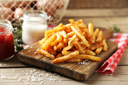 Tasty french fries on cutting board, on wooden table background Stock Photo
