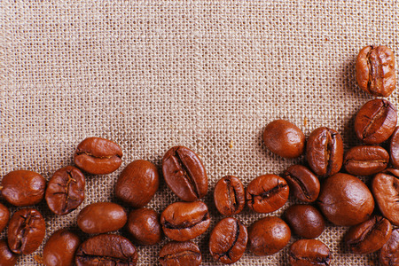 Frame of coffee beans on color sackcloth background Stock Photo