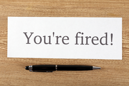 Message Youre Fired on sheet of paper with pen on wooden table, top view Stock Photo