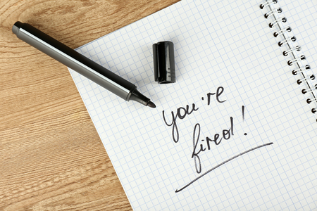 Message Youre Fired on notebook with marker on wooden table, closeup Stock Photo