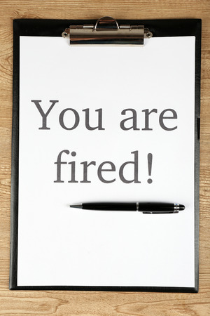 Message Youre Fired on clipboard on wooden table, closeup