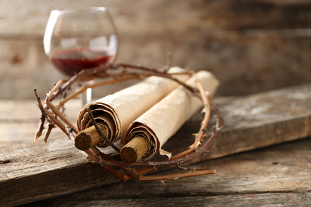 Crown of thorns, scroll and glass of wine on old wooden background Banco de Imagens