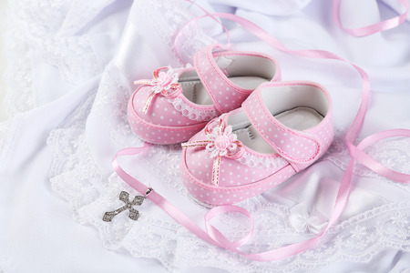 Baby shoe and cross for Christening Foto de archivo