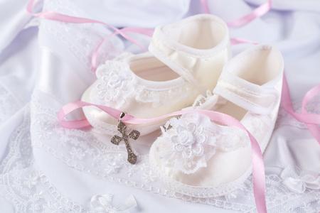 Baby shoe and cross for Christening Standard-Bild