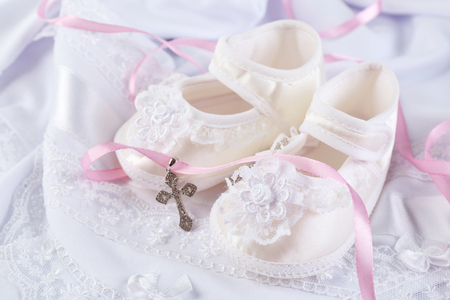 Baby shoe and cross for Christening Foto de archivo - 100636356