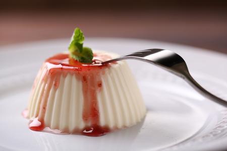 Tasty panna cotta dessert on plate, close up