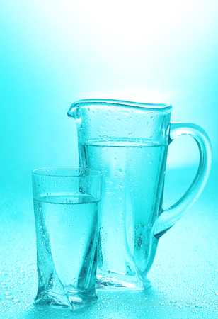 Glass pitcher and glass of water on blue background