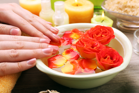Female hands with bowl of aroma spa water on wooden table, closeup Stock Photo