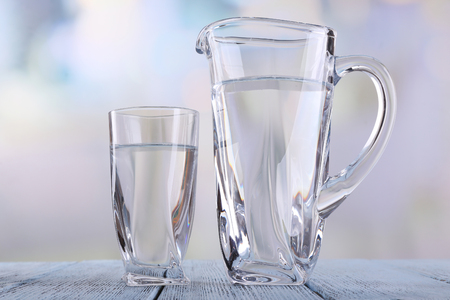 Glass pitcher and glass of water on wooden table on bright background