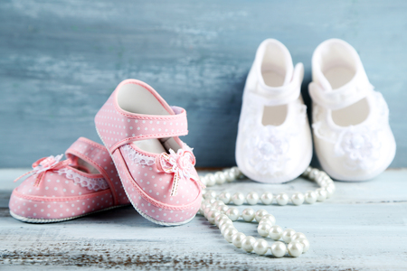 Pink and white toddler shoes on wooden background