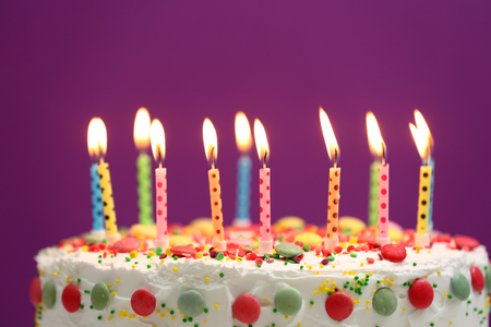 Birthday cake with candles on purple background Stock Photo